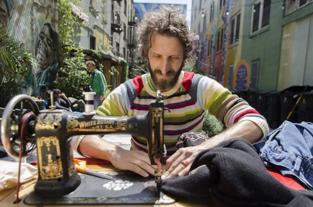 Michael+Swaine+mends+clothing+of+locals+in+the+Tenderloin+National+Forest+the+afternoon+of+April+15%2C+2012.+Swaine+comes+out+once+a+month+and+offers+his+services+to+mend+clothing+for+anyone+who+needs+it.+Photo+by+Gil+Riego+Jr.