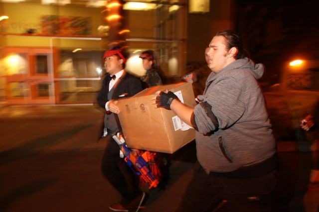 Steven Benitez (right) carry a box to complete a mission during the Humans vs. Zombies season 3 opener, 'Return to Night,' Oct. 23, 2013. Photo by Tony Santos / Xpress