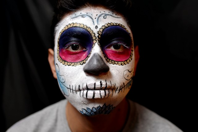 Chris Sanchez poses as a sugar skull for his Halloween costume on a budget. Used on Sanchez was white and black cream makeup, blue and gold pigments, a painter's palette, and brushes. All together this Halloween look costs around $10 - $15 while looking at different prices and bargins among Target, Walgrees, and Spirit Halloween. Photo by Virginia Tieman / Xpress