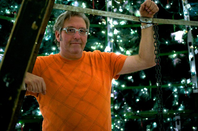 Edward Dahl stands in the center of the forty-foot-tall Barrango Christmas tree he and his team set up in Stonestown Galleria for the holiday. Photo by Kate O'Neal / Xpress