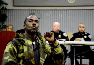 A community member by the name of Kilo G holds up a fist in front of a panel of SFPD members including Police Chief Greg Suhr during a community forum regarding the death of Mario Woods.