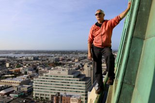 John Law demonstrates how he scales the Tribune Tower in orderto fix its LED lights on the outside in Oakland, Calif. on Thursday April 14, 2016. Law works at the tower, fixing its many clocks and their LED lights. This isn't part of  his usual urban exploring adventures but it does satisfy the thrill of doing something as exciting. (Aleah Fajardo/ Xpress)