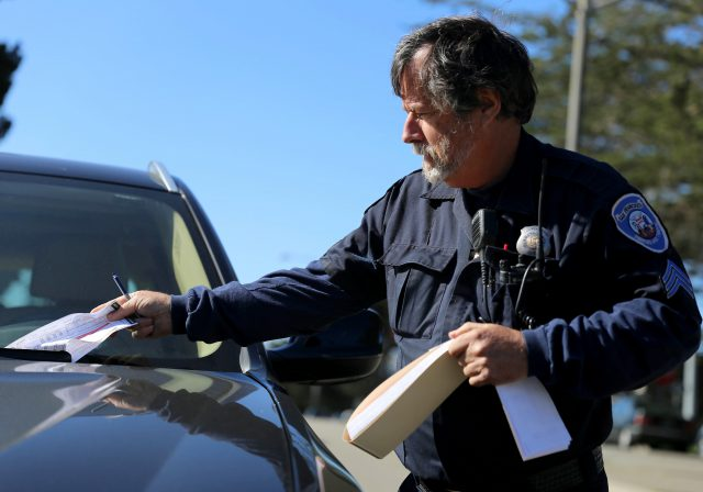 Bill Kettle writes parking tickets for cars violating the street sweeping signs in San Francisco on Monday April 25, 2016. (Aleah Fajardo/ Xpress)