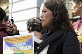 Veronica Mieto and her two-month-old Gael Isaih Comunidad stand of the steps of San Francisco City Hall during immigrant family day at on Thursday, April 28, 2016. Mieto is wearing headphones to receive translation of what speakers are saying. ( Ryan McNulty / Xpress )