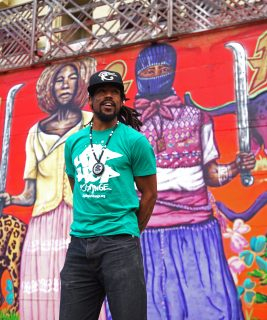 Khafre Jay, the founder and excutive director of Hip Hop for Change, poses for a portrait photo in front of the mural of HipHopForChange Inc. at Oakland, San Francisco, CA. on Tuesday, Sept. 13, 2016. (Perng-chih Huang/Xpress)