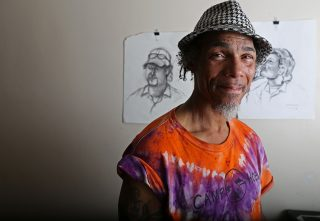 Ronnie Goodman stands in front of some portraits he drew of inmates while doing time in San Quintin State Prison. Aleah Fajardo/ Xpress