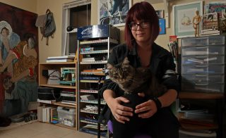 Amanda Campbell with her cat, Skiddy, in her home studio. Amanda adopted Skiddy as a therapy animal and helps her cope with her depression and anxiety. Aleah Fajardo/ Xpress