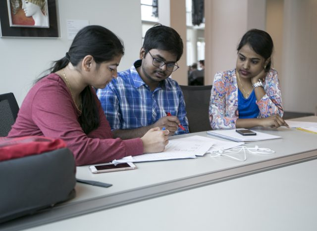 Priyanka Salvi (left) Sairoop Dasaraju (center) Bhavana Yadav (right) collaborate on an Industrial finances assignement at J. Paul Leonard Library at SF State on Apr. 16, 2017. (Ryan Zaragoza / Xpress).