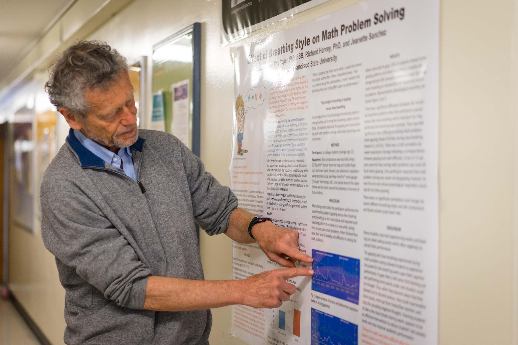 Erik Perper points to a poster on breathing techniques in the Humanities Building at SF State on Monday, April 17, 2017 (Sarahbeth Maney).