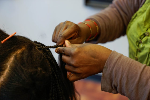 Sia Amma braids a weave into her clients hair at her salon, SF African Hair in the Tenderloin district on Wednesday, March 7. (Amarah Hernandez/ Xpress)