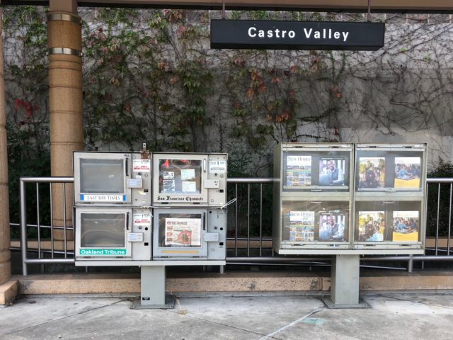 Newspaper dispensaries outside the Castro Valley BART station sit empty.