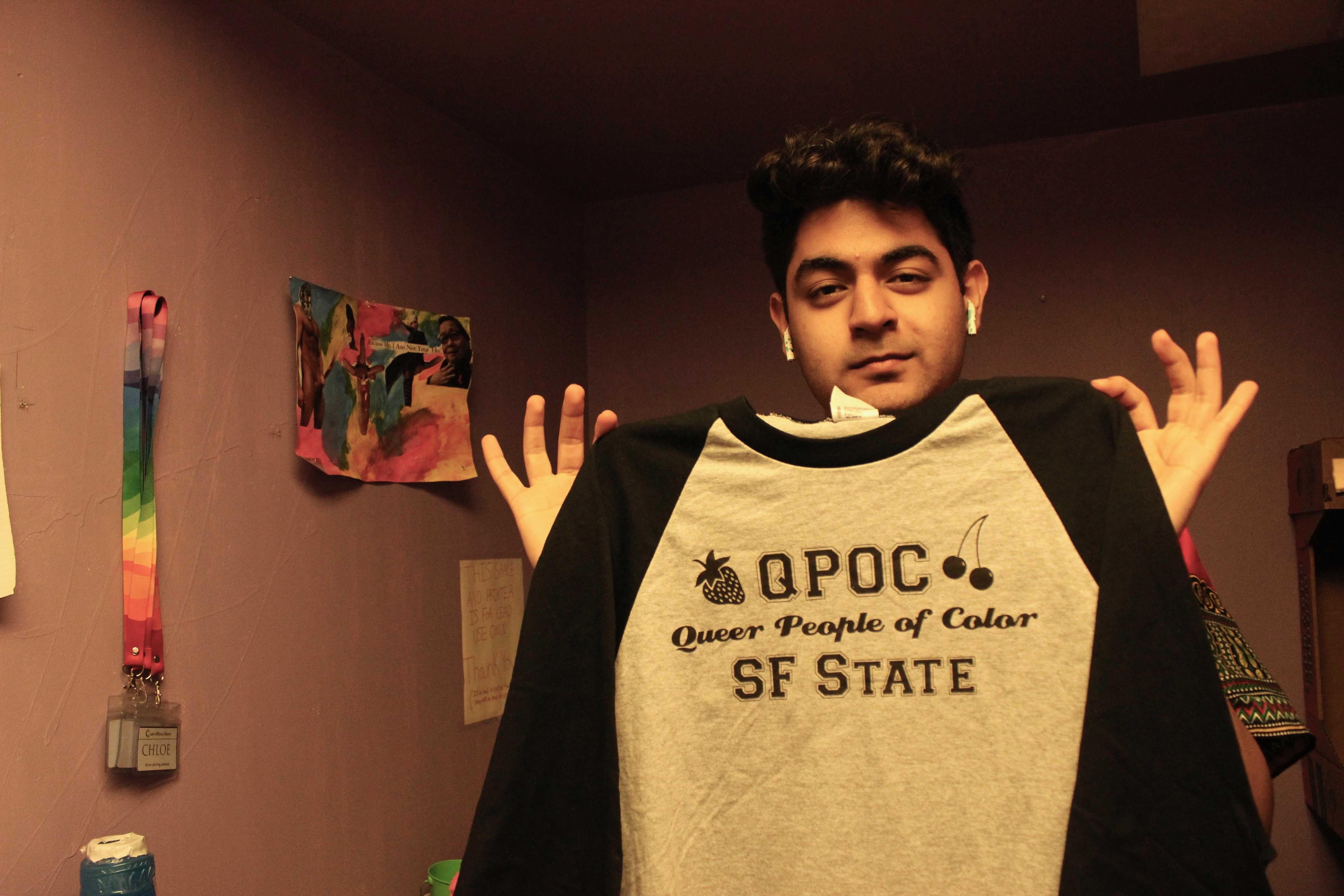 Ashesh Arora, the Director of Events for the Queer Alliance, holds the new shirt for Queer People of Color.