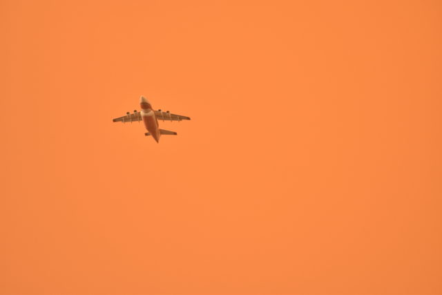 A fire-fighting airtanker flies through a smoke-filled sky as it battles the Carr Fire in Redding, California on July 27, 2018. (Boone Ashworth/Xpress)
