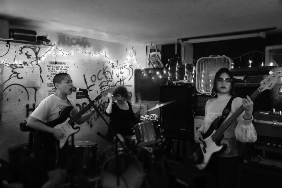 (Left to Right) Monica Ramos, singer/guitarist, Aimee Belden, drummer, and Krista Delosreyes, bassist also known as D.R.A.M.A. are practicing in their shared space on Sept. 30. 2019.