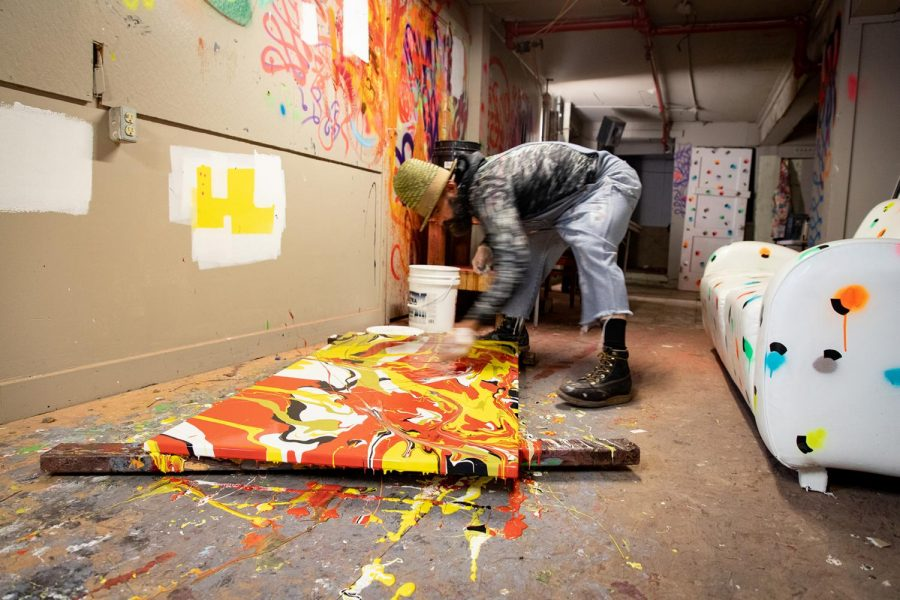 Pictured is Brett Vanhorn reaching across the canvas to pick up a side to allow the paint to drip in the direction he wants. Photographed on February 18, 2020 in San Francisco, Calif. (Maddison October / Xpress Magazine)