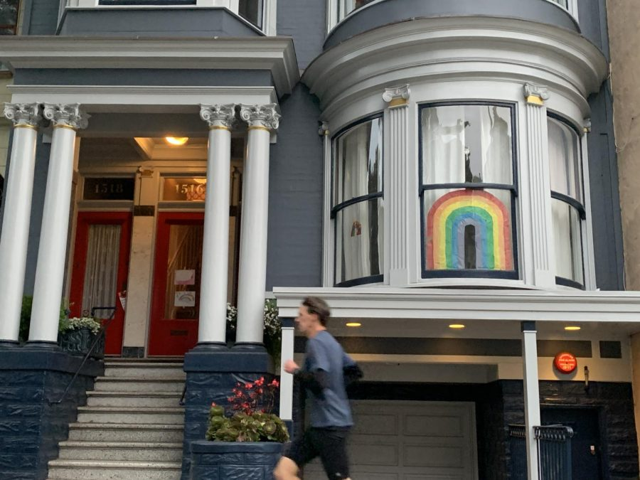 A lone runner jogs past a large rainbow near Haight St.