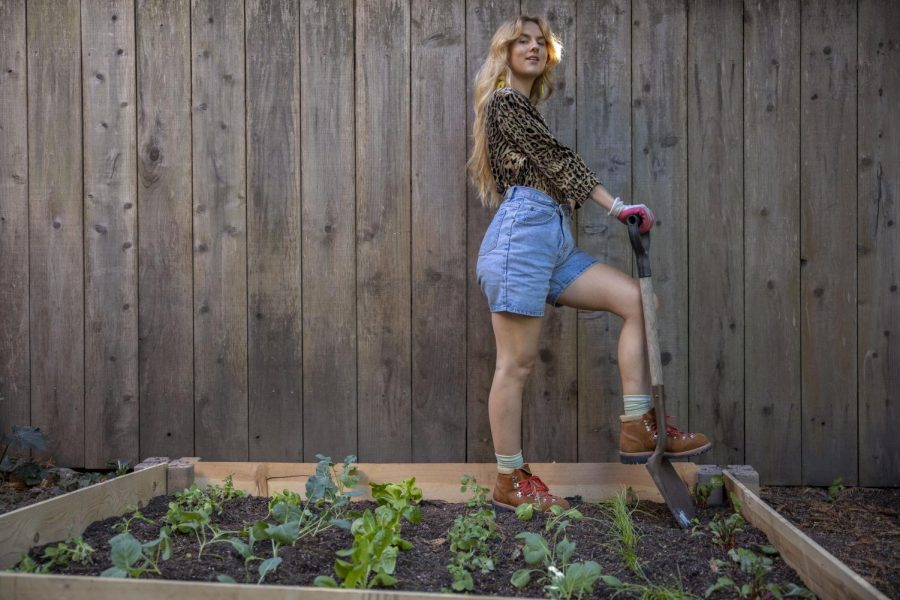 "Hannah Adams holds a shovel while standing alongside her vegetable garden project that she created during quarantine in Berkeley on Oct. 4, 2020. (Emily Curiel / Xpress Media)  During quarantine, Adams says that having plants helps with mental and physical health. ""It has absolutely helped me out! Even outside of the pandemic, they provide me clean air, they provide me a sense of stability, something to nurture and love and take care of. I would say regarding my vegetable garden that I just started it was definitely a wonderful quarantine project to keep myself preoccupied and off my phone. And really spend time in solitude just with momma Earth."""