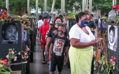 """A family slowly winds through the """"Say Their Names"""" exhibit installed at Klyde Warren Park. Many attendees recorded their experiences on camera in Dallas, Texas. (Omar Morales / Xpress Magazine)"""