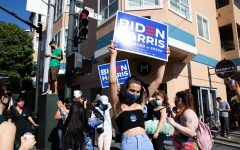 Jupiter Peraza waves a Biden-Harris 2020 sign outside of her work, Manny's, which held one of San Francisco's many Biden block parties on the corner of 16th St. and Valencia Ave. on Saturday, Nov. 7, 2020. (Saylor Nedelman / Xpress Magazine)