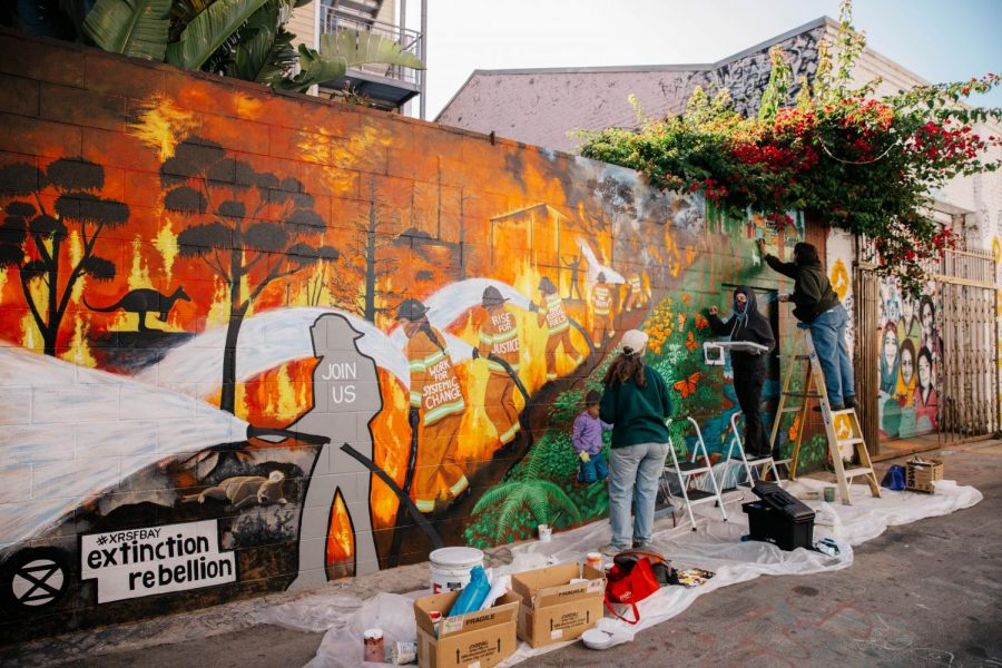 Lisa-Zimmer Chu, Jamie Northrup, and Jeanne Leimkuhler paint the natural wildlife section of the mural on Nov. 7, 2020, the day of President-elect Joe Biden's confirmation. Valencia Street, where Clarion Alley is located, was crowded with San Franciscans celebrating his victory. (Saylor Nedelman / Xpress Magazine)