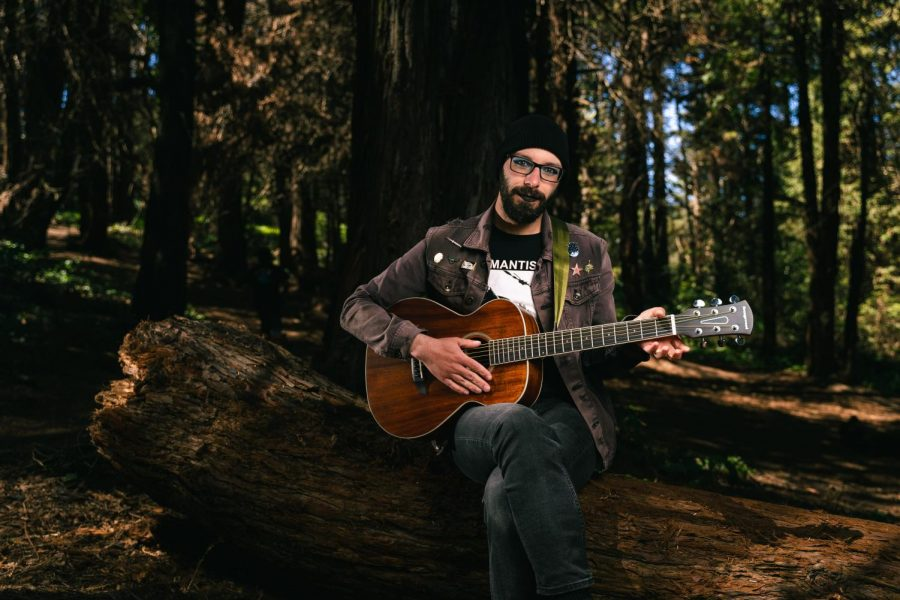 Nina Marie Larson (they/them) plays the guitar near the McLaren Park Redwood Grove Playground. Larson has played the guitar on and off for about 11 years and plans to form a band in the coming year. (Jun Ueda / Xpress Magazine)