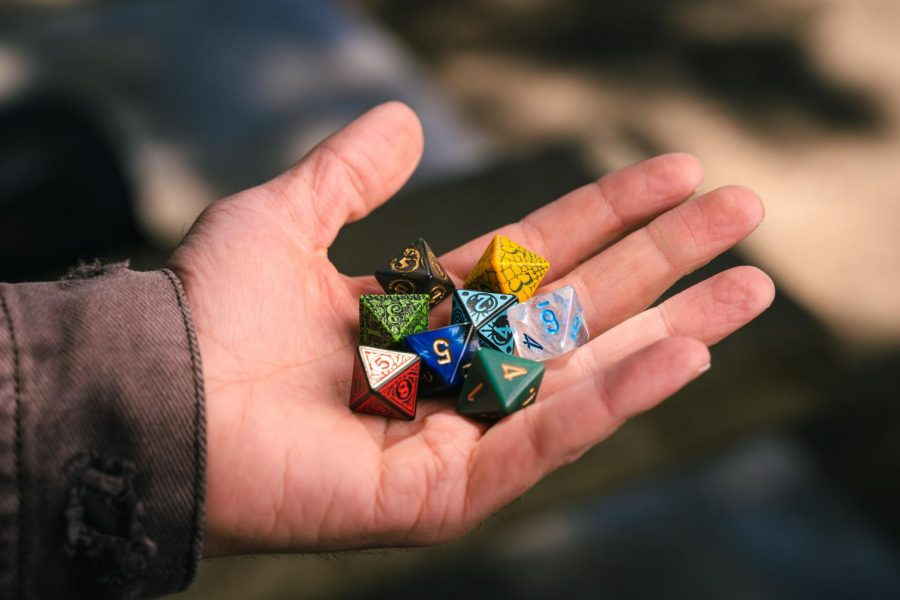"""Nina Marie Larson holds various eight-sided dies (also known as """"D8"""") used primarily for Dungeons and Dragons, a popular tablet op role-playing game. Larson partakes in many game nights with their friends and expresses the importance of building a bond with others through these games. (Jun Ueda / Xpress Magazine)"""
