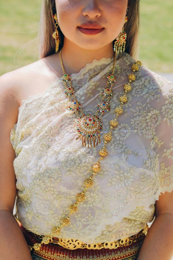 "Jasmine Nguyen, wears a traditional Thai outfit called ""Chut Thai"". It means ""Thai Outfit"" and can be worn by men, women, and children. Nguyen said that Chut Thai for women usually consists of a pha nung or a pha chung hang, a blouse, and a pha biang. (Sydney Welch / Xpress Magazine)"