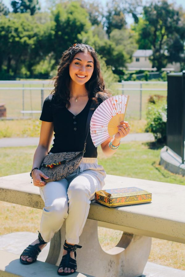Sarah Naini, holds a manual fan that was given to her by her grandma. It has printed cherry blossoms. The cherry blossom symbolizes a time of renewal since they only bloom in early April after the long, winter cold. (Sydney Welch / Xpress Magazine)