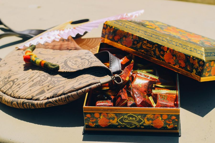 "Iranian sweets are displayed in a decorative box along side an Iranian hand bag and a South Korean hand-held fan. ""When I was younger and my grandparents would visit from Iran, they always brought a bag full of Iranian sweets because they knew they were my favorite. The candy reminds me of my grandparents who hold a special place in my heart,"
