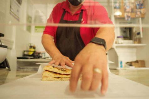Michael Soracco wraps an order of Focaccia in parchment paper at Liguria Bakery on Thursday, Oct. 7, 2021 in San Francisco, Calif. (Cameron Lee / Xpress Magazine)